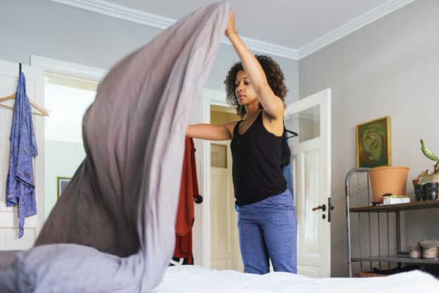 Woman making bed at home